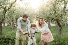 La giovani mamma e papà insegnano al loro figlio a guidare una bici immagini stock libere da diritti
