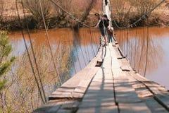 La giovani mamma, papà e figlia della famiglia camminano sul vecchio ponte sospeso sopra il fiume Immagini Stock Libere da Diritti