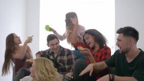 La gioventù divertendosi e mangiare la pizza con le bevande che si siedono sullo strato, amici felici canta le canzoni con una ch