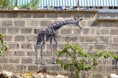 La giraffa attinge una parete dei blocchi crudi Fotografie Stock