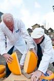 La giuria che taglia il formaggio al mercato del formaggio a Alkmaar immagine stock libera da diritti