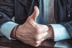 La giusta mano maschio con un rosario sul polso e su un pollice si ? alzata su Primo piano immagini stock