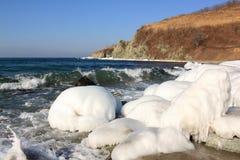 La glace a couvert des pierres sur le bord de la mer Photographie stock libre de droits