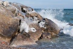 La glace a couvert des roches sur une plage en hiver Image libre de droits