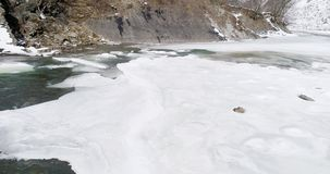 La glace d'og de vue aérienne fond - les écoulements de rivière Vue d'une rivière de montagne dans les Carpathiens en hiver banque de vidéos