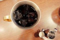 La glace de vue supérieure de plan rapproché de l'americano, café noir glacé contenu dans une tasse de cuivre a servi avec le sir Image libre de droits