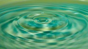 La goccia dell'acqua o del liquido ha creato un'ondulazione immagini stock libere da diritti