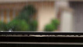 La goccia di pioggia che cade sulla balaustra del balcone e spruzza l'acqua stock footage