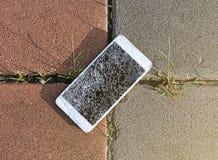 La goccia rotta del telefono cellulare sulla pietra ha pavimentato il marciapiede fuori fotografia stock libera da diritti