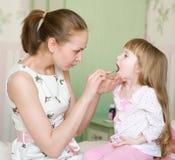 La gola della bambina d'esame della madre immagine stock