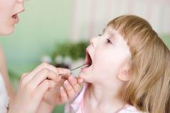 La gola della ragazza d'esame del pediatra immagini stock