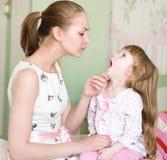 La gola della ragazza d'esame della giovane madre immagine stock libera da diritti