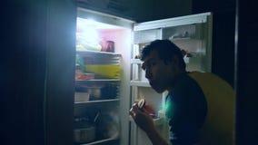 La gola di dieta dell'uomo mangia alla notte dal frigorifero l'uomo apre all'interno il frigorifero ed il frigorifero stock footage