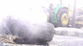 La gomma di automobile brucia e fuma sulla strada nella città Messo su fuoco durante il evenement politico video d archivio