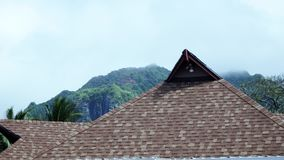 La gomma grigio ardesia ha piastrellato il tetto e la montagna nebbiosa fotografia stock