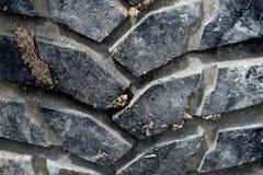 La gomma nera del primo piano fuori dall'automobile della strada ha suolo sporco immagine stock