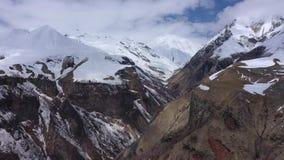 La gorge parmi les montagnes couronnées de neige du Caucase banque de vidéos