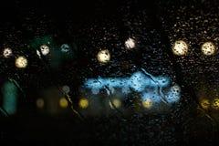 La gota de lluvia en la ventana y el bokeh empañan el extracto del fondo Imagen de archivo