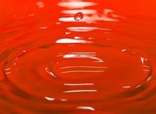 La gota en agua roja imágenes de archivo libres de regalías