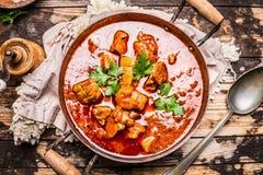 La goulache ou le ragoût dans le pot de vintage avec des tomtoes sauce sur le fond en bois rustique photo stock