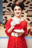La goupille de charme vers le haut de la fille boit du café en rétro café Images stock