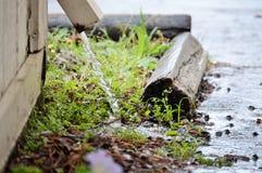 La gouttière répand l'eau de pluie Image libre de droits