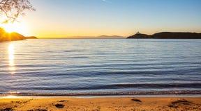 La Grèce, île de Kea, coucher du soleil à la plage Sun tombant, paysage marin avec le phare images libres de droits