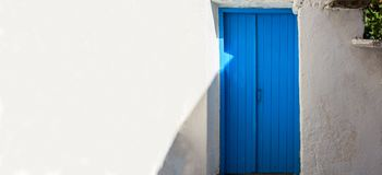 La Grèce, île de Kea Porte bleue en bois sur le fond blanc de mur Photos libres de droits