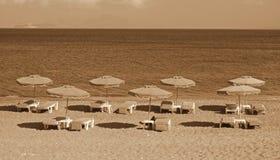 La Grèce La Grèce Kefalos Présidences et parapluies sur la plage Photographie stock