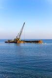 La grúa de elevación descarga piedras en el mar Foto de archivo