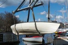 La grúa del barco levanta el barco en el agua Fotos de archivo libres de regalías