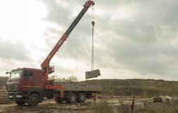 La grúa del camión descarga los bloques de cemento Fotografía de archivo