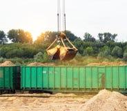 La grúa del puerto hace el cargamento de pedazos de madera en los carros de la carga del tren, primer, cucharón, gancho agarrador fotos de archivo