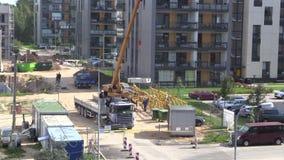 La grúa descarga el bloque del remolque del camión en emplazamiento de la obra almacen de metraje de vídeo