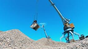 La grúa industrial lleva los escombros en un cubo del metal metrajes