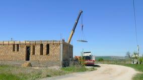 La grúa móvil arrastra el bloque de cemento a la casa inacabada metrajes