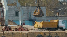 La grúa portuaria con las ayudas grises cerca del río carga la arena del cubo del gancho agarrador en el camión, un camión volque almacen de video