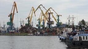 La grúa portuaria funciona con la chatarra; actúe encendido el embarcadero en puerto comercial almacen de metraje de vídeo