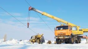 La grúa sostiene el cable para la línea de alto voltaje entre nieve debajo del cielo azul metrajes