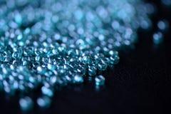 La graine dispersée perle la couleur bleu vert sur une surface foncée Images stock