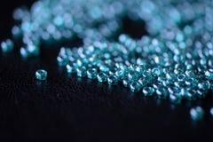 La graine dispersée perle la couleur bleu vert sur une surface foncée Image libre de droits