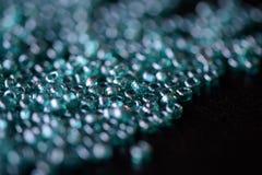 La graine dispersée perle la couleur bleu vert sur une surface foncée Photos libres de droits