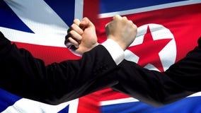 La Gran Bretagna contro confronto della Corea del Nord, pugni sul fondo della bandiera, diplomazia fotografia stock