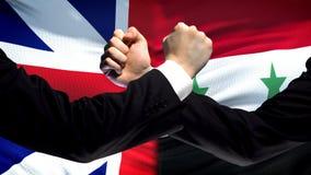 La Gran Bretagna contro confronto della Siria, pugni sul fondo della bandiera, diplomazia immagini stock