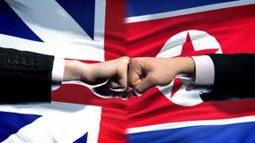 La Gran Bretagna contro il conflitto della Corea del Nord, pugni sul fondo della bandiera, diplomazia fotografie stock libere da diritti