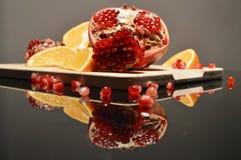 La granada y la naranja acuña en un tablero de madera imagen de archivo
