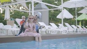 La grand-mère étreint sa petite-fille s'asseyant par la piscine et le regard à la caméra Le grand-père repose le mensonge sur un  banque de vidéos