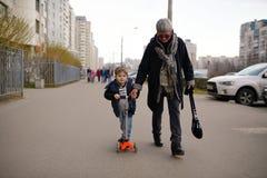 La grand-mère abaisse le petit-fils sur la rue de scooter photos libres de droits