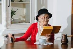 La grand-mère aimable lit son livre à la table de dîner à la maison photographie stock libre de droits