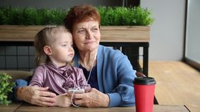 La grand-mère avec sa petite-fille écoutent la musique dans les écouteurs du téléphone banque de vidéos